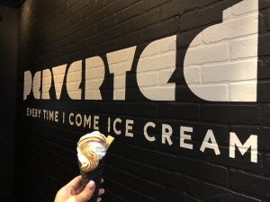 Perverted ice cream cone in front of store wall
