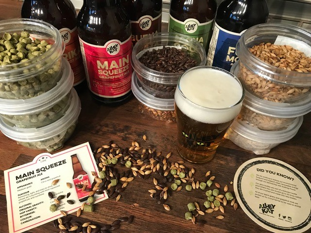 beer ingredients and a glass of beer on a table