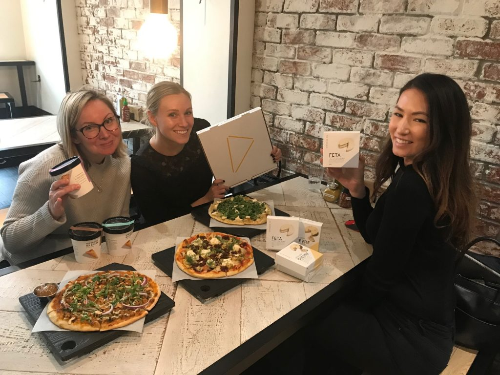 three women enjoying pizza and holding virtuous pie's pizza box