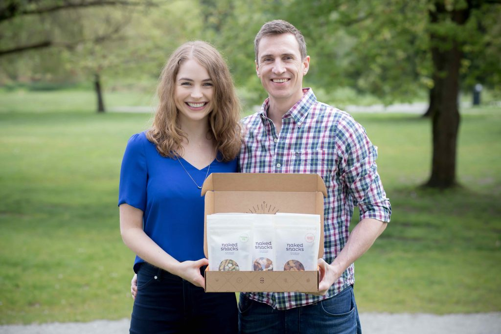 Naked Snacks founders holding a box of their products