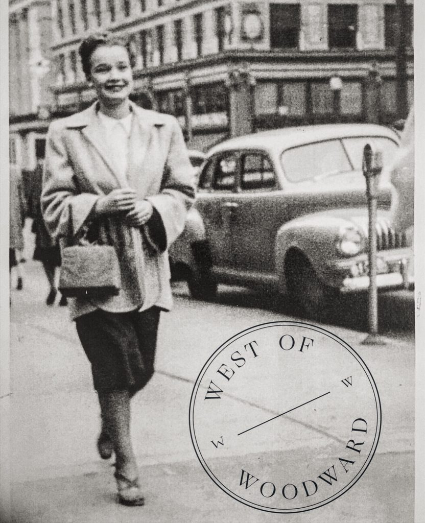 Black and white old photo of a woman walking down the street with the West of Woodward logo on the corner